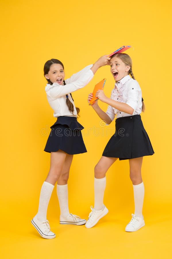 Schoolgirls fight. outraged classmates with workbook. girls can`t share a book. kids learning grammar. back to school. Information. love reading. childrens stock photography