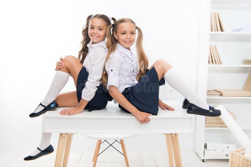 Schoolgirls friends sit on desk. Best friends relaxing. Schoolgirls tidy hairstyle relaxing having rest. School uniform royalty free stock image