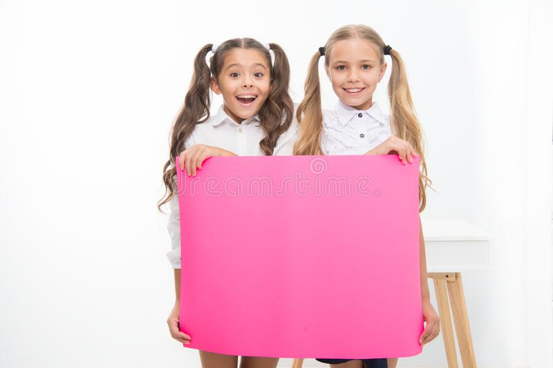 Schoolgirls hold advertisement poster copy space. Children hold advertising banner. Happy pupils children with blank. Paper for advertisement. School news stock photo