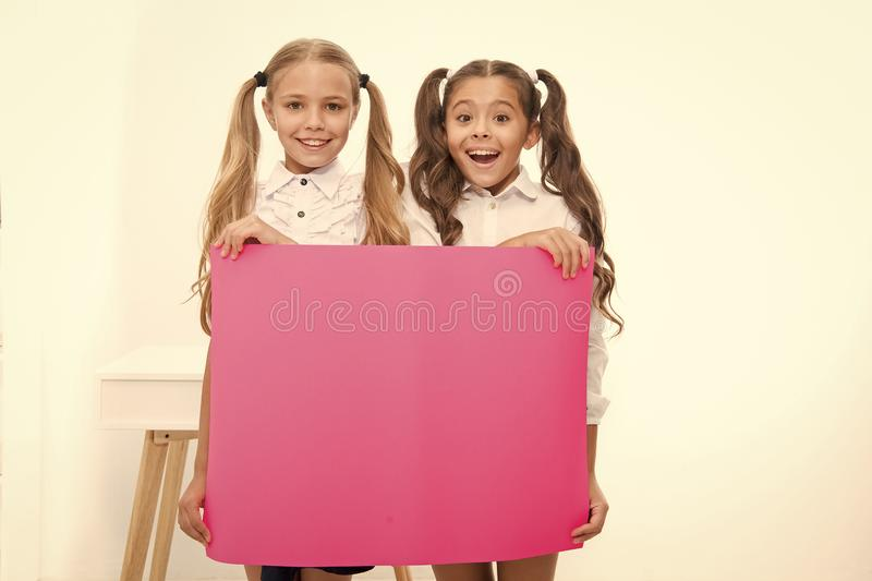 Schoolgirls hold advertisement poster copy space. Children hold advertising banner. Happy pupils children with blank. Paper for advertisement. School news stock image