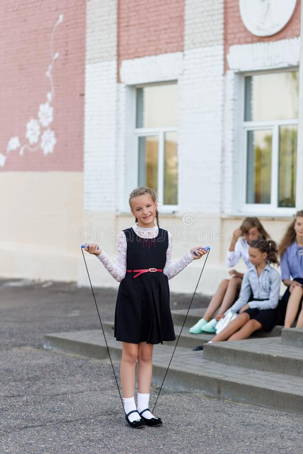 Schoolgirls jump on a rope at a change in front of the school. School style royalty free stock photos