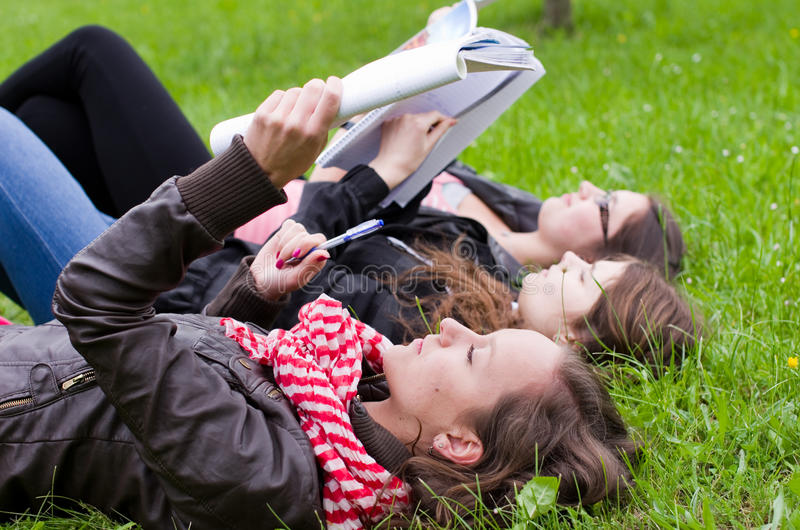 Schoolgirls learning. Outdoors on a grass stock photos