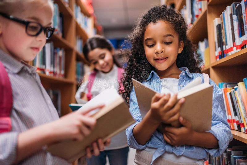 Schoolgirls looking for books in library. Beautiful little schoolgirls looking for books in library stock photo