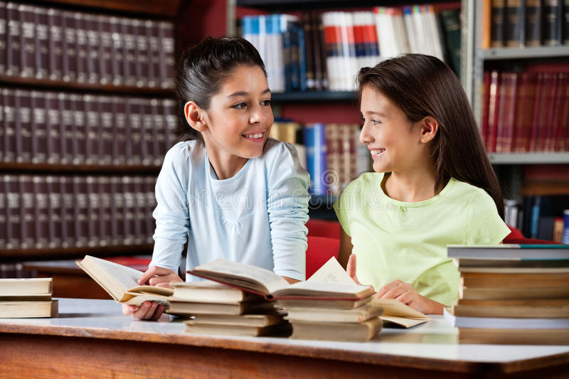 Schoolgirls Looking At Each Other While Studying stock image