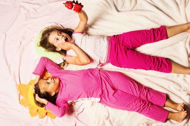 Schoolgirls over slept lying on funny pillows. Children with shocked faces lie on pink background holding alarm clock. Kids in pink pajamas, put hands up stock photography