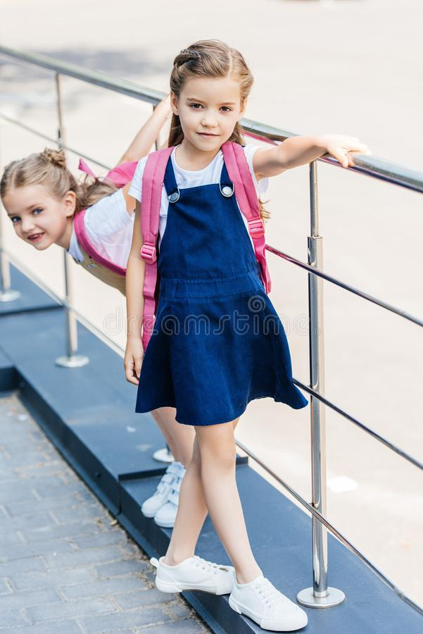 schoolgirls with pink backpacks playing stock photos