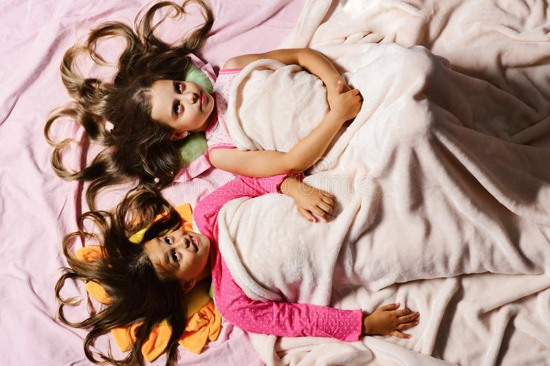 Schoolgirls in pink pajamas wallow on colorful pillows, topview royalty free stock images