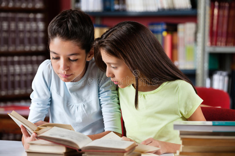Schoolgirls Reading Book Together In Library royalty free stock photo