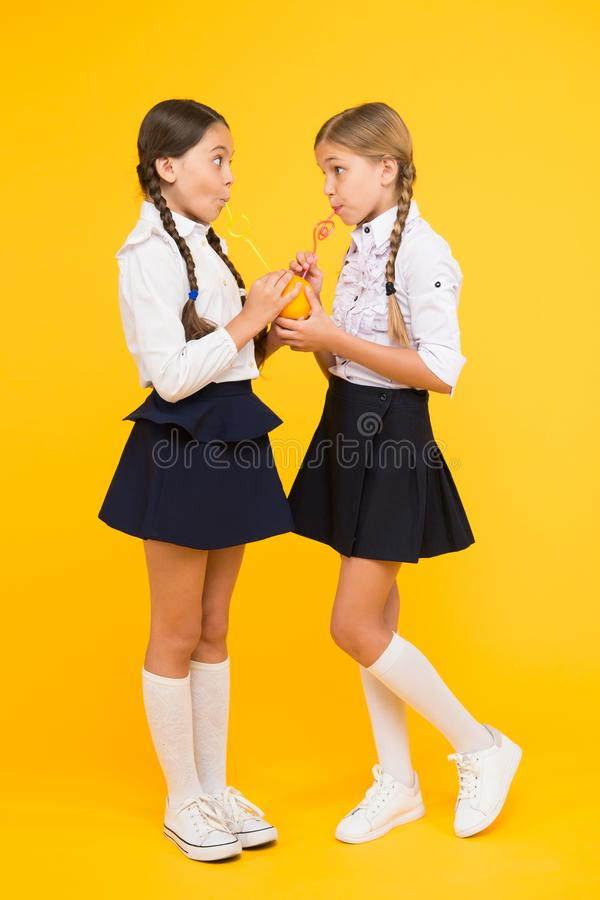 Schoolgirls sharing lunch. Healthy food. Vital habits. Fruits glucose energy source. School lunch. Vitamin nutrition. Fresh fruit school. Girls kids school stock image