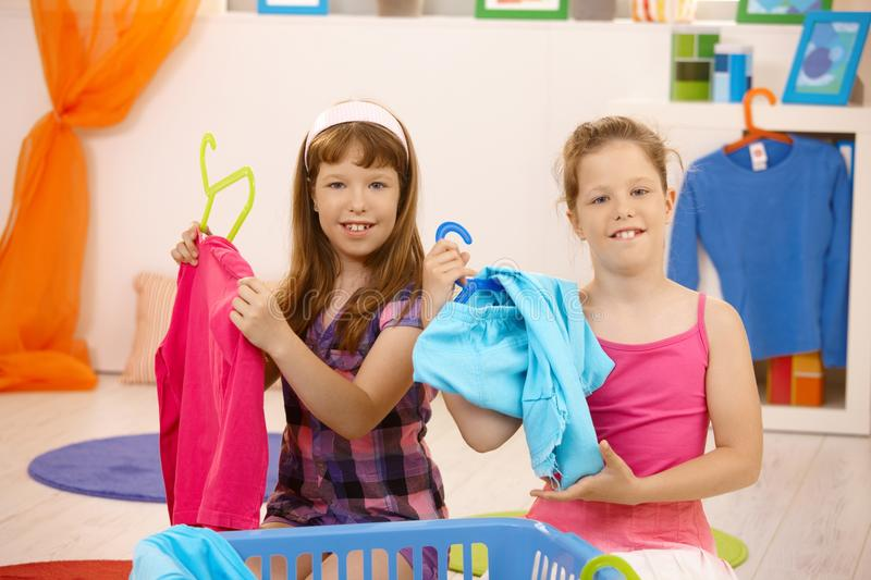 Download Schoolgirls Sorting Clothes At Home Stock Photo - Image of contact, brown: 18493140
