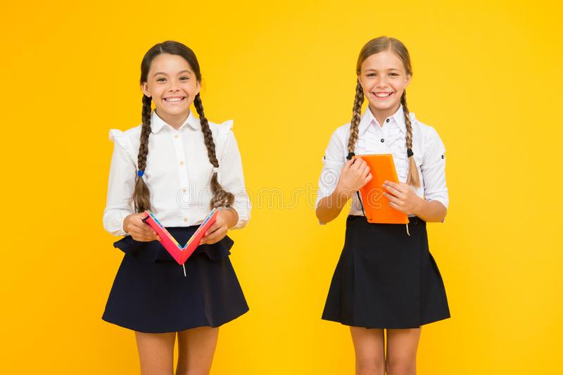 Schoolgirls study together on yellow background. Study language. Cute children study with textbook. Practice and improve royalty free stock images