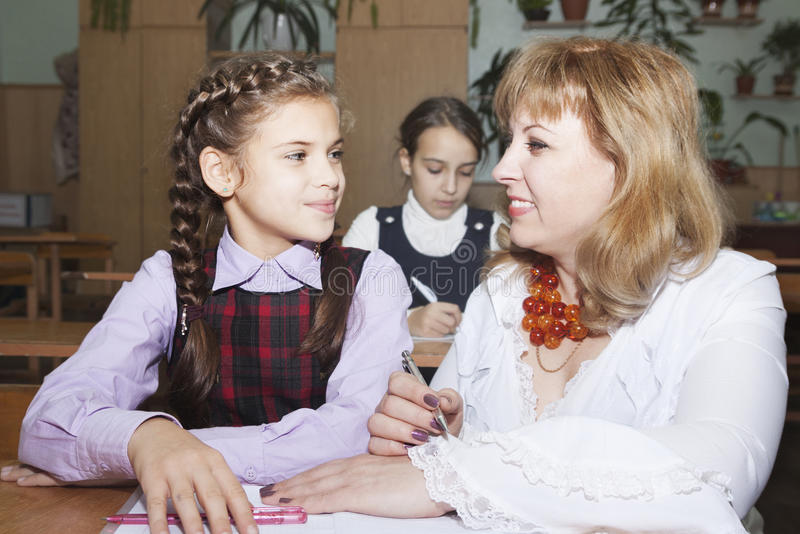 Schoolgirls and teacher. Teacher explains students in the classroom stock image