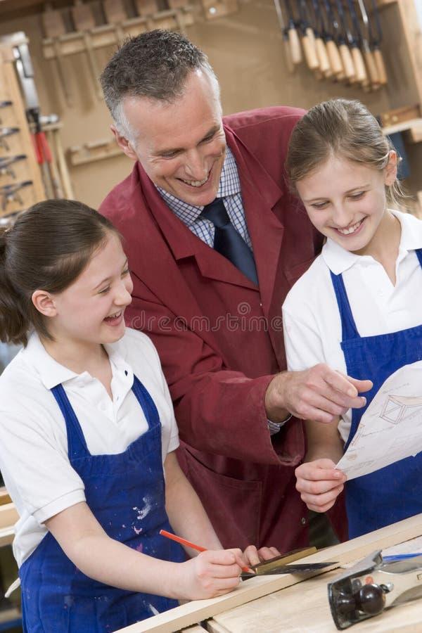 Schoolgirls and teacher in woodwork class stock image