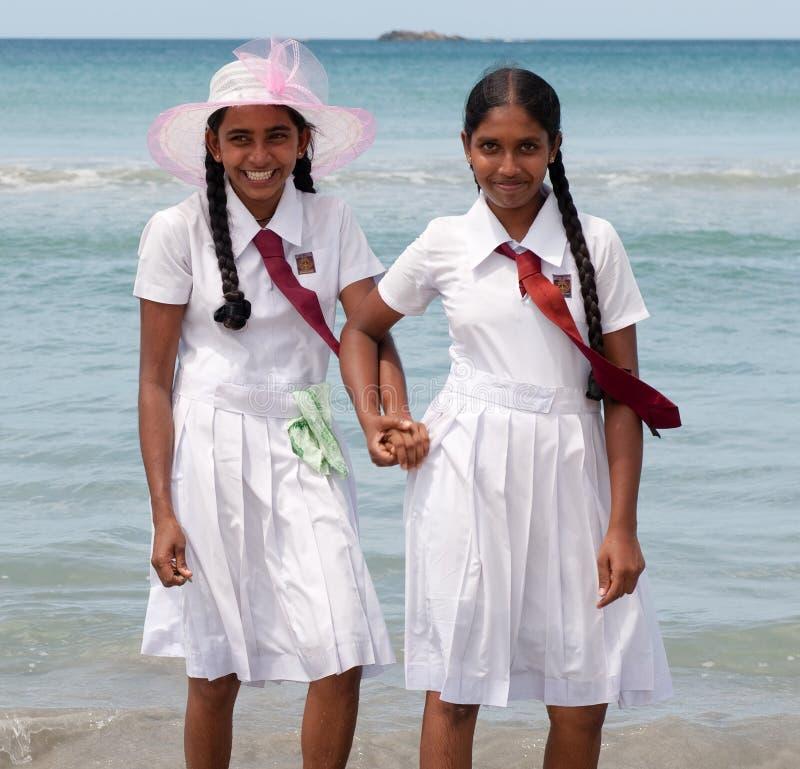 Schoolgirls in uniform hand in hand royalty free stock images