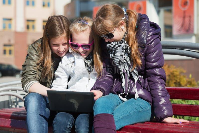 Schoolgirls using laptop. Teenage schoolgirls using laptop on the bench stock image