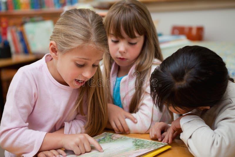 Schoolgirlsläsning en saga tillsammans royaltyfri fotografi