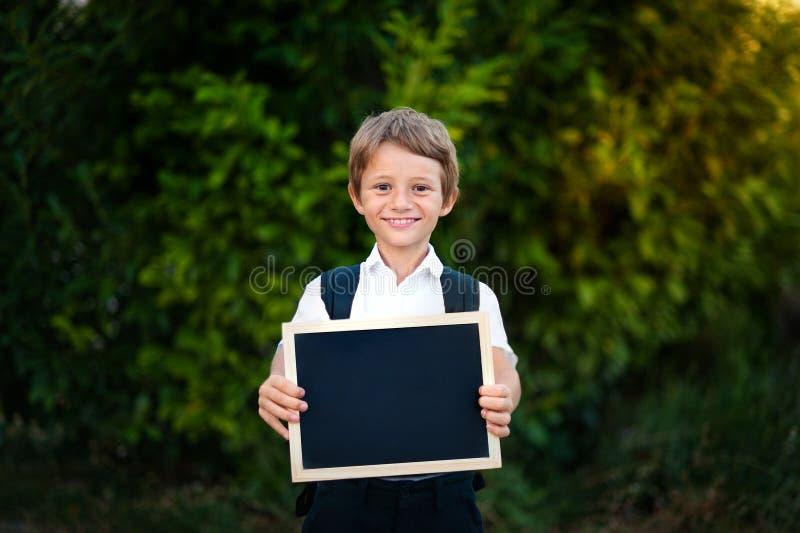 Schooljong geitje die een bord met terug naar schoolbericht houden stock afbeeldingen