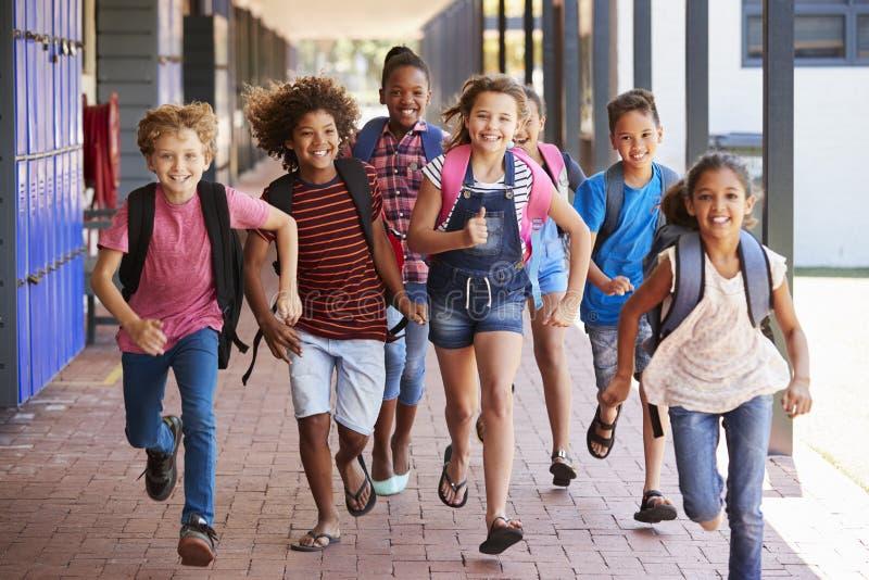 Schooljonge geitjes die in basisschoolgang lopen, vooraanzicht royalty-vrije stock fotografie