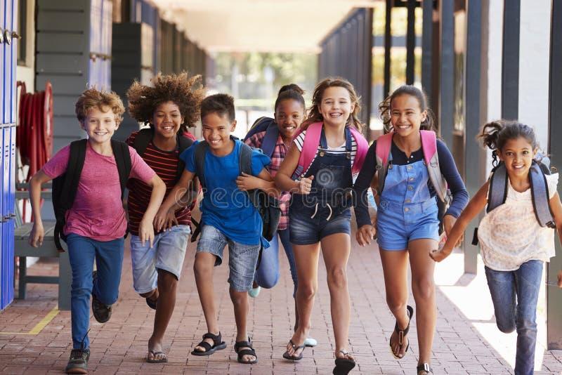 Schooljonge geitjes die in basisschoolgang lopen, vooraanzicht stock afbeeldingen