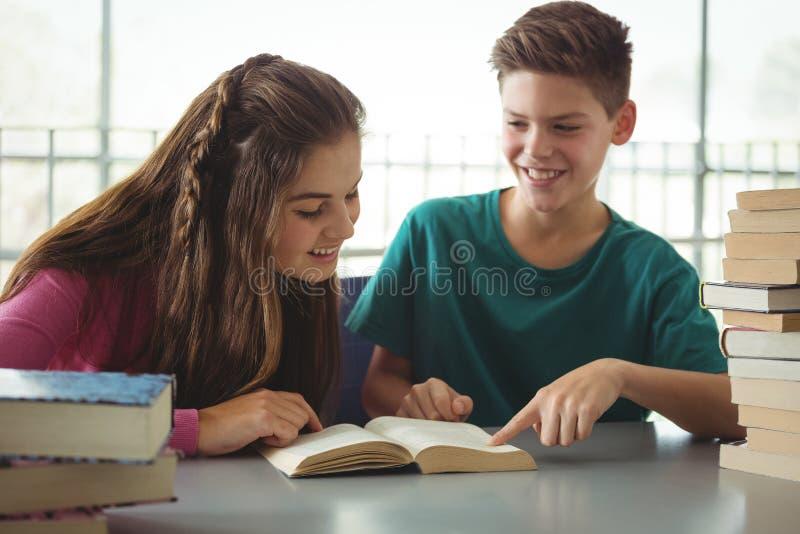 Schooljonge geitjes die boeken in bibliotheek lezen op school stock foto's