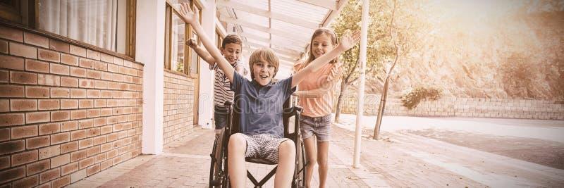 Schooljonge geitjes die een jongen op rolstoel duwen stock afbeelding