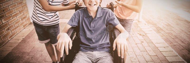 Schooljonge geitjes die een jongen op rolstoel duwen royalty-vrije stock afbeeldingen