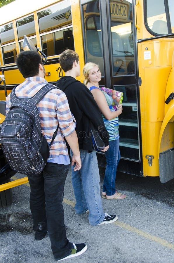 Schooljonge geitjes die op de bus wachten te krijgen royalty-vrije stock afbeeldingen