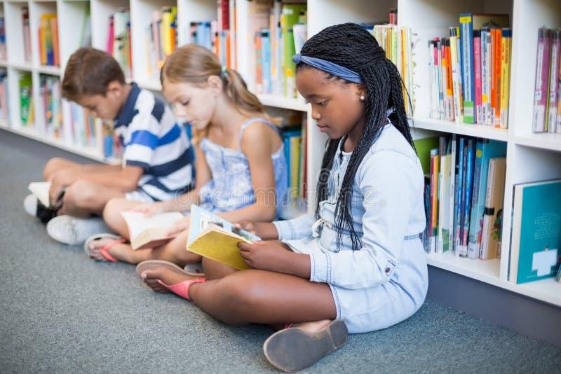 Schooljonge geitjes die op vloer zitten en boek in bibliotheek lezen royalty-vrije stock afbeelding