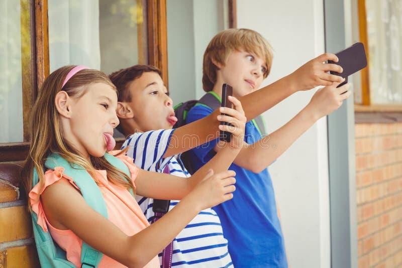 Schooljonge geitjes die selfie met mobiele telefoon in gang nemen stock foto