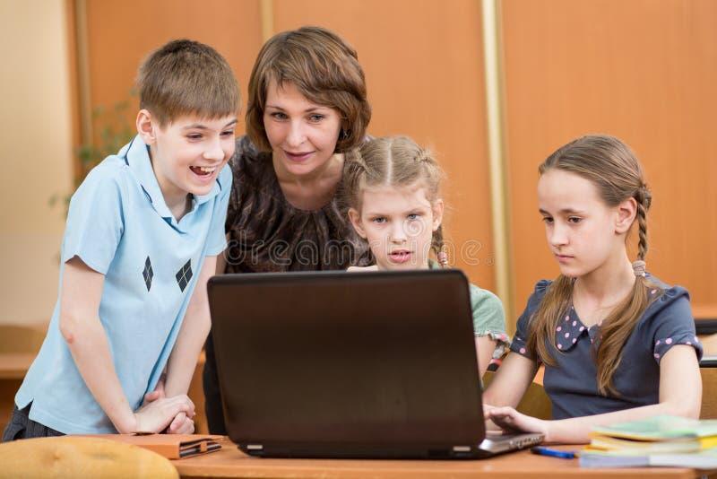 Schooljonge geitjes en leraar die laptop met behulp van bij les stock afbeelding