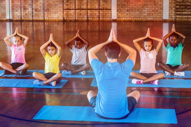 Schooljonge geitjes en leraar die tijdens yogaklasse mediteren royalty-vrije stock fotografie