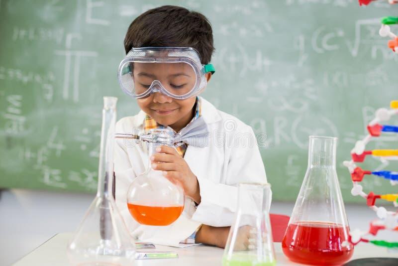 Schooljongen die een chemisch experiment in laboratorium doen stock foto