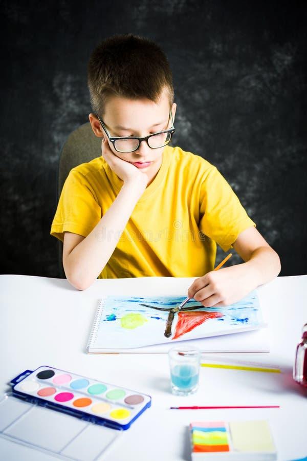 Schooljongen die een kleurrijke tekening thuis maken stock afbeeldingen