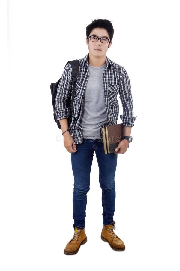 Schooljongen die een rugzak en boeken dragen royalty-vrije stock afbeelding