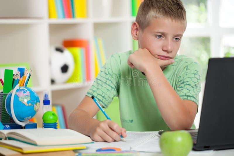 Schooljongen die en laptop bestuderen bekijken stock fotografie