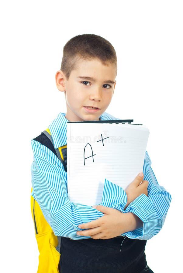 Schooljongen die goed testresultaat houdt stock afbeeldingen