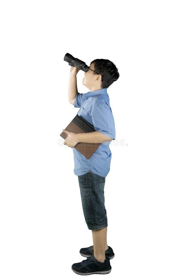 Schooljongen die iets met binoculair bekijken royalty-vrije stock afbeelding
