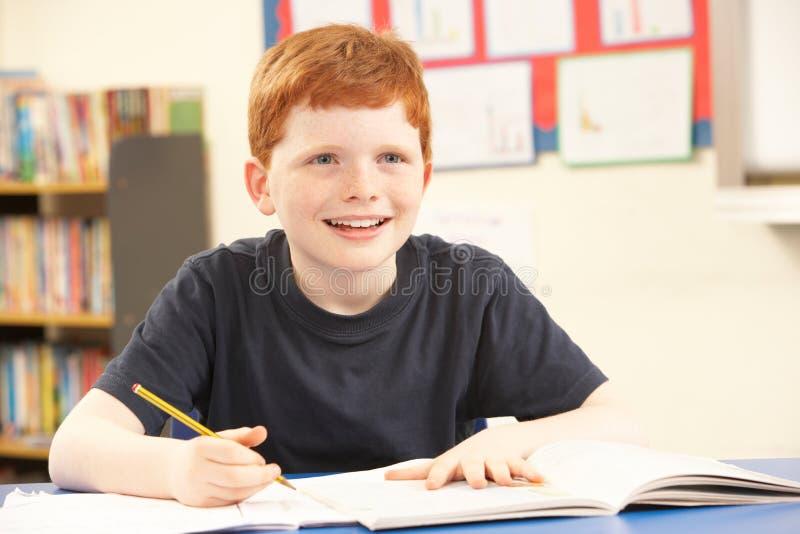 Schooljongen die in Klaslokaal bestudeert royalty-vrije stock foto