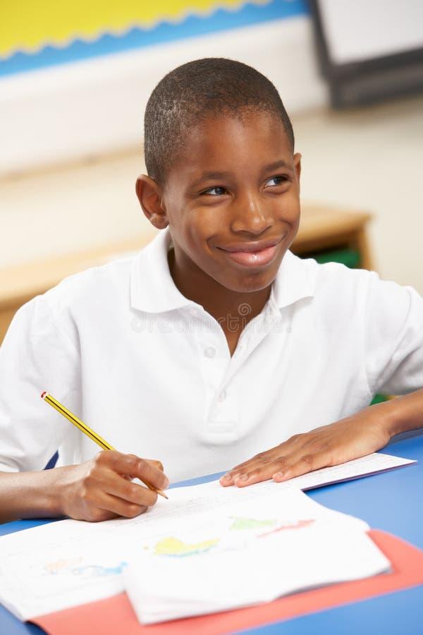 Schooljongen die in Klaslokaal bestudeert royalty-vrije stock fotografie