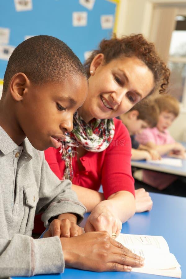 Schooljongen die in Klaslokaal bestudeert stock afbeelding