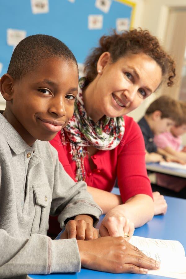 Schooljongen die in Klaslokaal met Leraar bestudeert royalty-vrije stock foto's