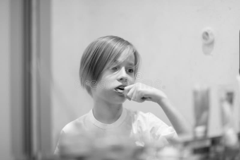 Schooljongen die met modieus kapsel zijn tanden borstelen royalty-vrije stock afbeelding