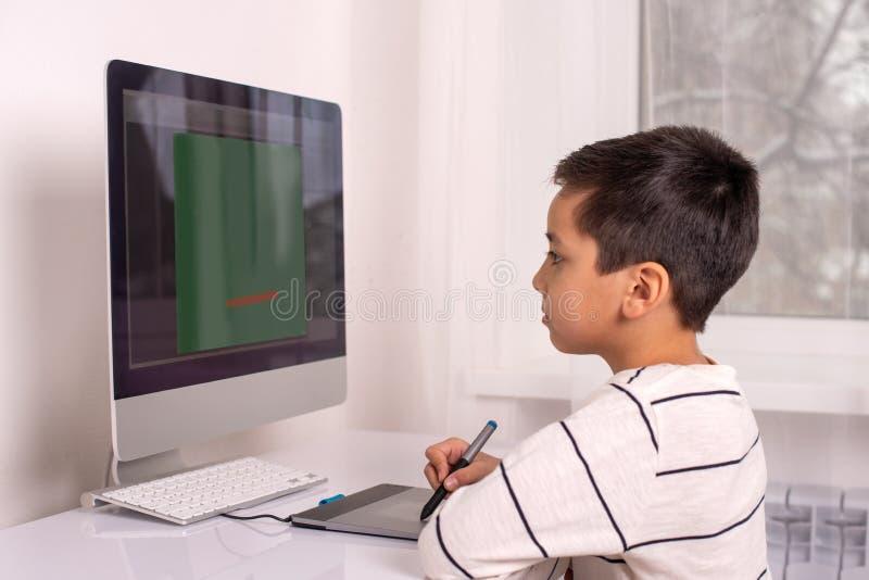 Schooljongen die op een computer trekken die een tablet gebruiken royalty-vrije stock foto