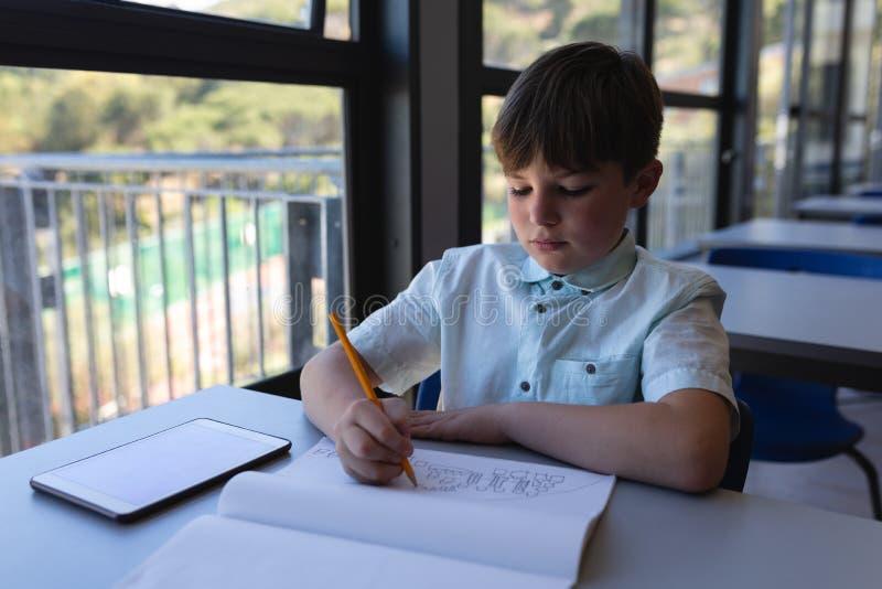 Schooljongen die op notitieboekje bij bureau in klaslokaal trekken stock fotografie
