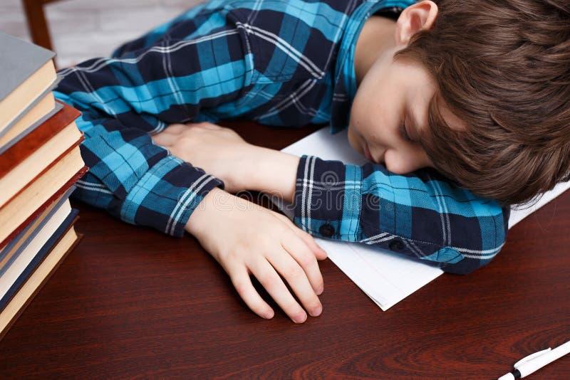 Schooljongen die in slaap terwijl het bestuderen bij voorbeeldenboek vallen Het schoolleven stock afbeeldingen