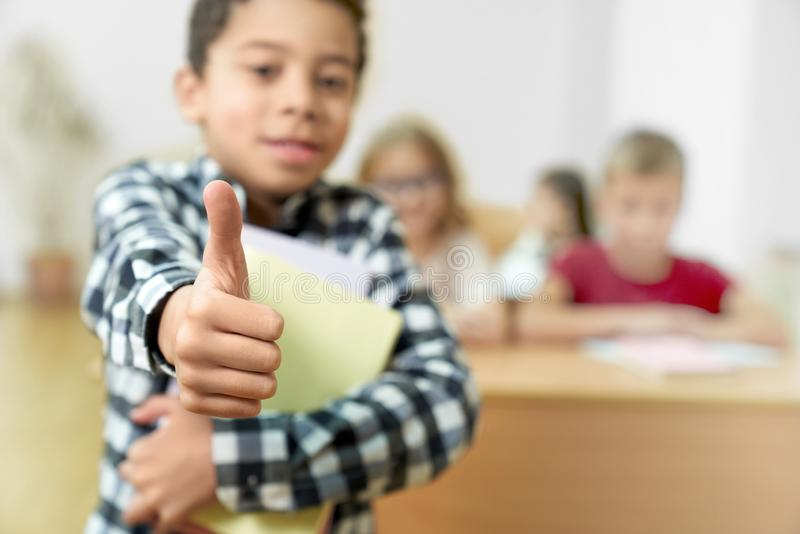 Schooljongen die zich in klasse bevinden die duim tonen royalty-vrije stock afbeelding