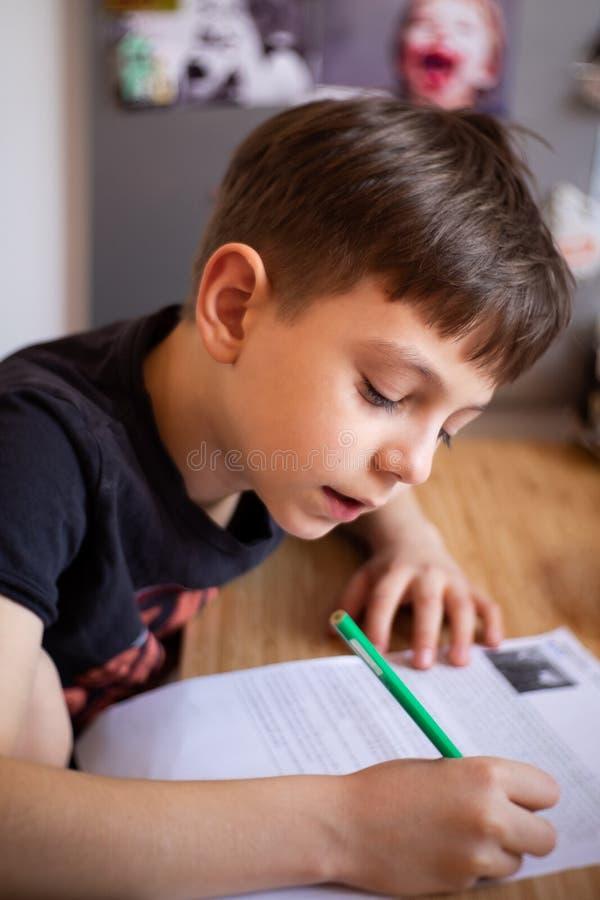 Schooljongen die zijn thuiswerk maken stock foto