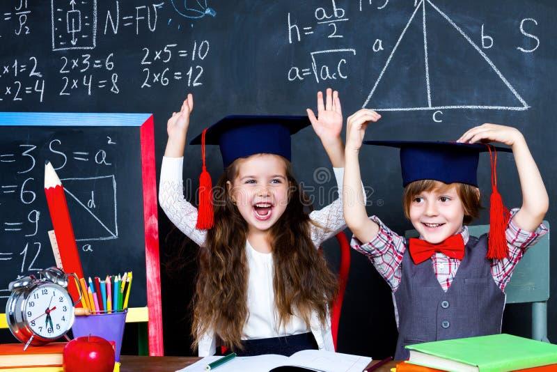 Schooljongen en schoolmeisje in klaslokaal op school stock fotografie