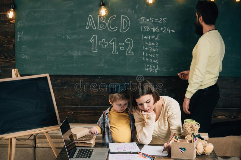 Schooljongen in klasse De schooljongen leert tekening Weinig schooljongen heeft les met leraar en privé-leraar De schooljongen on stock foto's