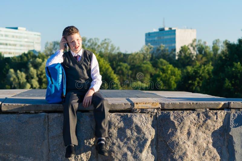 Schooljongen met een rugzak zitting en het spreken op de telefoon royalty-vrije stock foto's